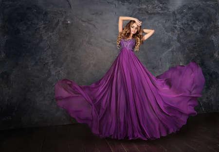 flyaway: oung beauty woman in fluttering  dress. Dance, movement. Long skirt flutters. Stock Photo