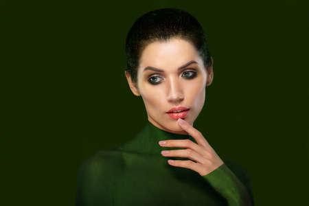 femme romantique: Portrait d'une belle femme sur un fond vert. Close-up visage. penser. Thumb près des lèvres.