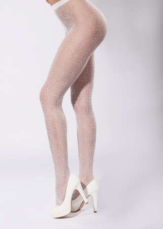 fine legs: Long beautiful legs in fishnet stockings and white shoes.
