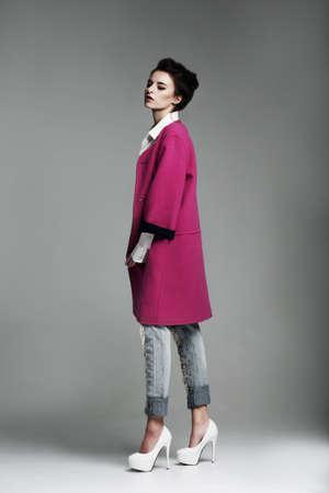 full height: Female model posing in a crimson coat. Fashion. Woman, Full height.