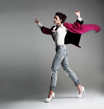 moda ropa: Hermosa mujer elegante con un abrigo de moda, camina en el estudio. ropa de volar. Moda.
