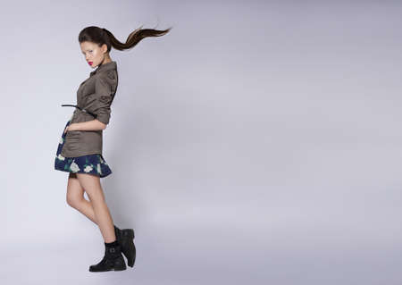 khaki:  Girl in a full-length jacket. Fashion, Street style, teen fashion. Stock Photo