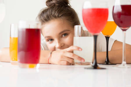 Girl smiling, Multicolored glasses of juices and drinks.
