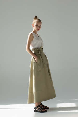 Young woman posing in studio on a light background. Long green skirt, white summer T-shirt, black sandals. She stands sideways, hands in pockets. Reklamní fotografie