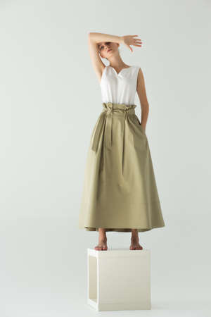 Woman model stands barefoot on a cube in the studio on a light background. Clothes - long skirt and white summer T-shirt. The arm is bent and covers her forehead. Reklamní fotografie