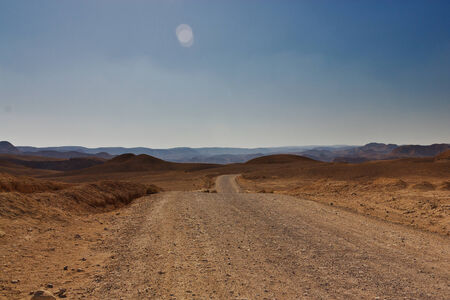Desert in midday, with long road Stock Photo