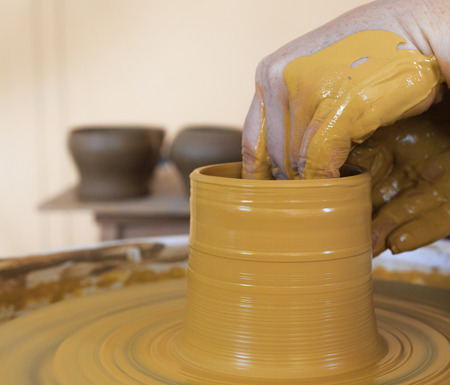 potters wheel: Hands working with clay on potters wheel. With two ready things on the background. Stock Photo
