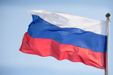 russian flag: Official russian flag on the blue sky background.