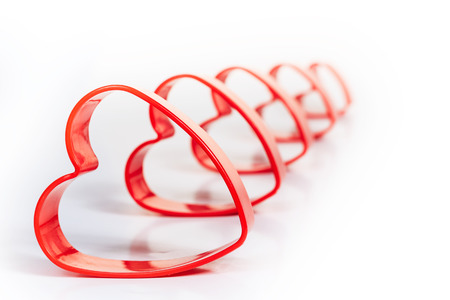 dof: Five red heart 3D shapes sequence isolated white with small DOF and blurred tail. Stock Photo