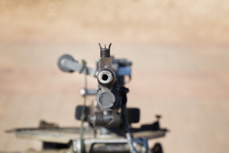 automatic machine: Weapon. Automatic machine gun directed toward. Small amount of focus. Focus put only on start of barrel. Small vignette put around of picture.