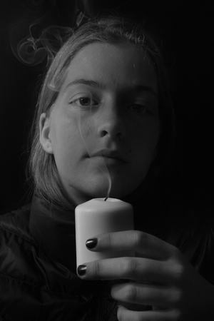 young girl models: Beautiful girl with extinguished candle smoked.