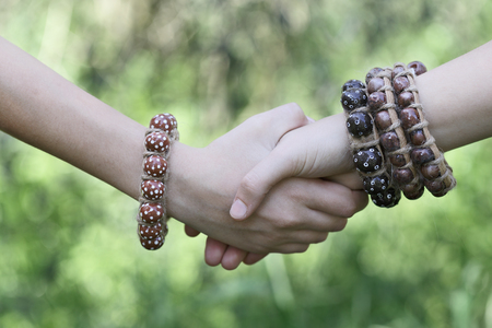 young womens: Young womens handshake, teenagers handshake in green nature background. Two hands together, with boho style jewelry, boho-chic.