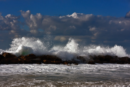 wavely: Sea storm on the sunset beach. Stones in the water. Stock Photo