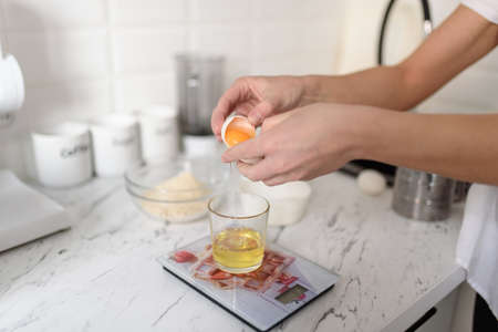 A woman separates egg yolks and whites for culinary and baking purposes