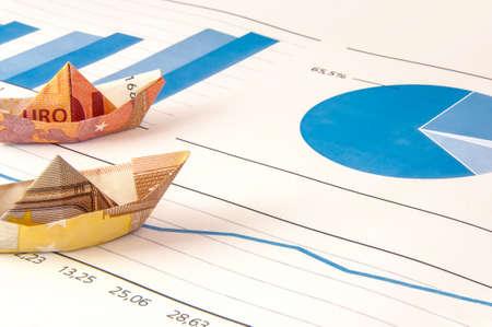 navire de papier portant l'argent le long du schéma de financement.