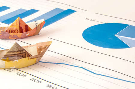Paper ship carrying money along the finance diagram.