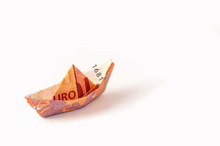 Dix euro bill plié en voilier, isolé sur blanc. Banque d'images