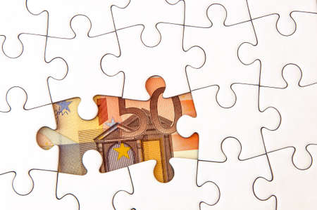 hidden taxes: 50 Euro money bill under a jigsaw puzzle with missing pieces. Stock Photo