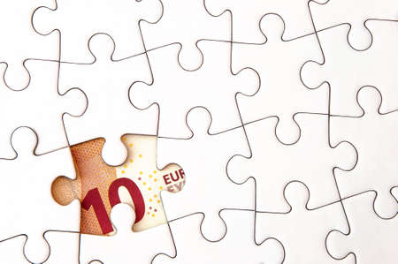 hidden taxes: 10 Euro money bill under a jigsaw puzzle with missing pieces. Stock Photo