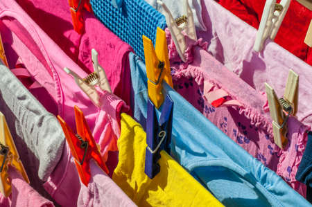 launder: Mixed clean laundry pinned with colourful clothespins Stock Photo