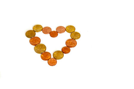 greediness: Heart created with coins on white background Stock Photo