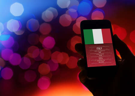 echnology: Hand holding a smartphone with information about Italy.