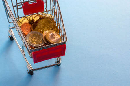 A shopping cart with euro coins, symbolic photo for purchasing power and consumption