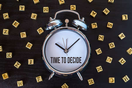 decide: Time to decide - Alarm clock on wooden table with letters Stock Photo