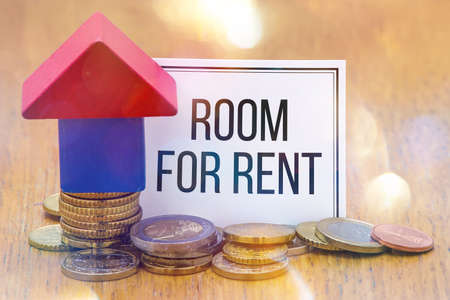 Words Room for Rent on a white paper with a Wooden House Blocks with Euro coins. Stock Photo