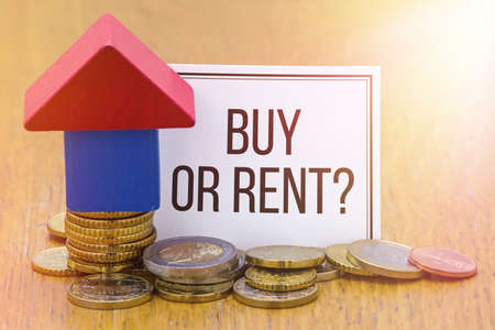 buying questions: Words Buy or Rent? on a white paper with a Wooden House Blocks with Euro coins.