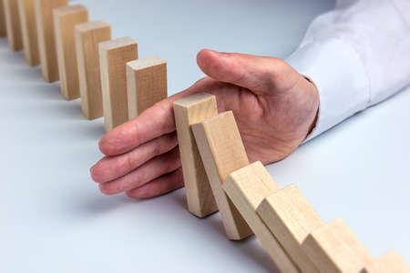 Stop Domino Effect - Hand Prevents Failure Stock Photo