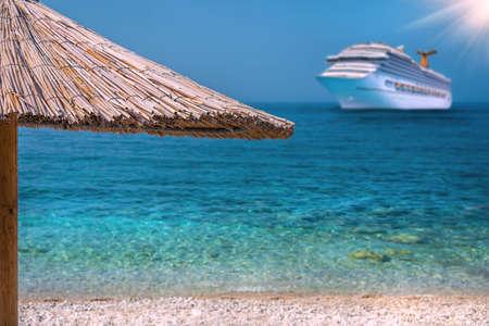 Belle plage avec un parapluie et un bateau de croisière Banque d'images