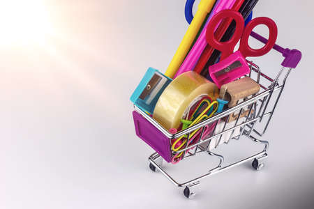school supplies in shopping cart on white background - back to school Stock Photo