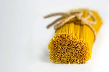 pâtes crues attachées avec une corde sur fond blanc