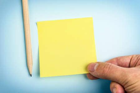 Main tenant du papier jaune Note et crayon Banque d'images