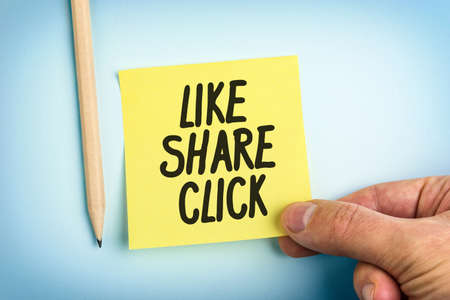Hand Holding Yellow Paper Note With Words Like Share Click Banque d'images