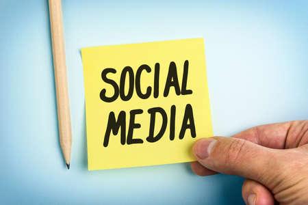 Hand Holding Livre jaune note avec des mots médias sociaux Banque d'images