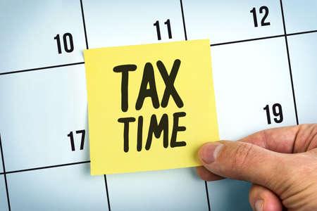 Main tenant le papier jaune Note avec les mots Durée de l'impôt sur le calendrier