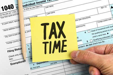 Main tenant le papier jaune Note avec les mots Tax Time