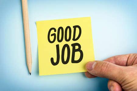 Une main tenant Livre jaune note avec des mots bon travail Banque d'images