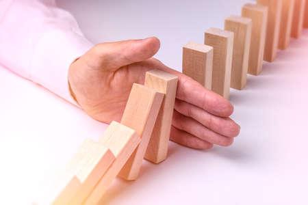Stop Domino Effect - Hand Prevents Failure Stock Photo