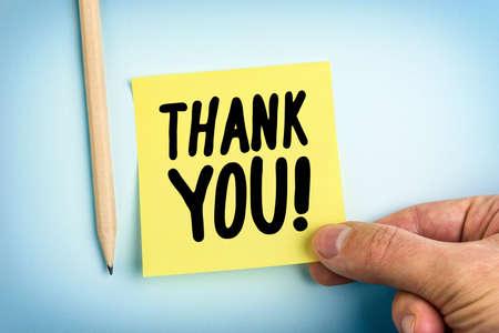Main tenant le papier jaune Note avec les mots Merci