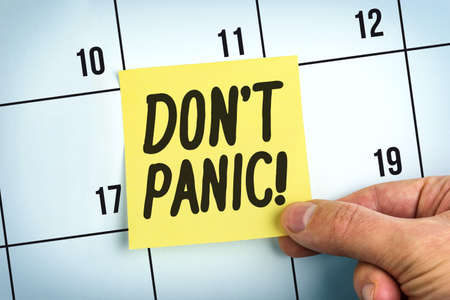 Hand Holding Yellow Paper Note With Words Don't Panic On Calendar