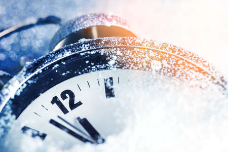 New Year Concept, Alarm Clock in the snow shows two minutes before twelve Stock Photo
