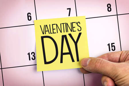 Hand Holding Yellow Paper Note With Words Valentine's Day On Calendar