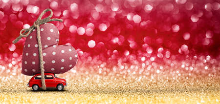 Valentines Day Incoming - Miniature Red Car Carrying Heart and Glitter Background