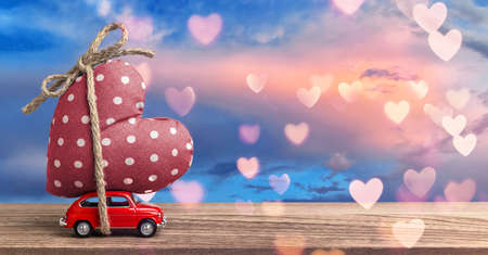 Valentines Day Incoming - Miniature Red Car Carrying Heart with Sky Background