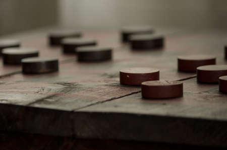 checker board: Damas rojo y negro de madera de la vendimia se sientan en un tablero de ajedrez r�stico. Foto de archivo
