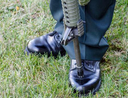 vigil: A gun barrel rests on black military shoes as a reservist stands vigil at a war memorial in Nova Scotia, Canada, Remembrance Day, November 11th, 2014.