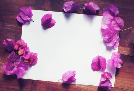 wedding table decor: White paper with pink and white flowers on a wooden desk top view Stock Photo
